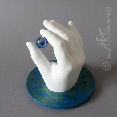 Kinderhand mit einer Glasmurmel